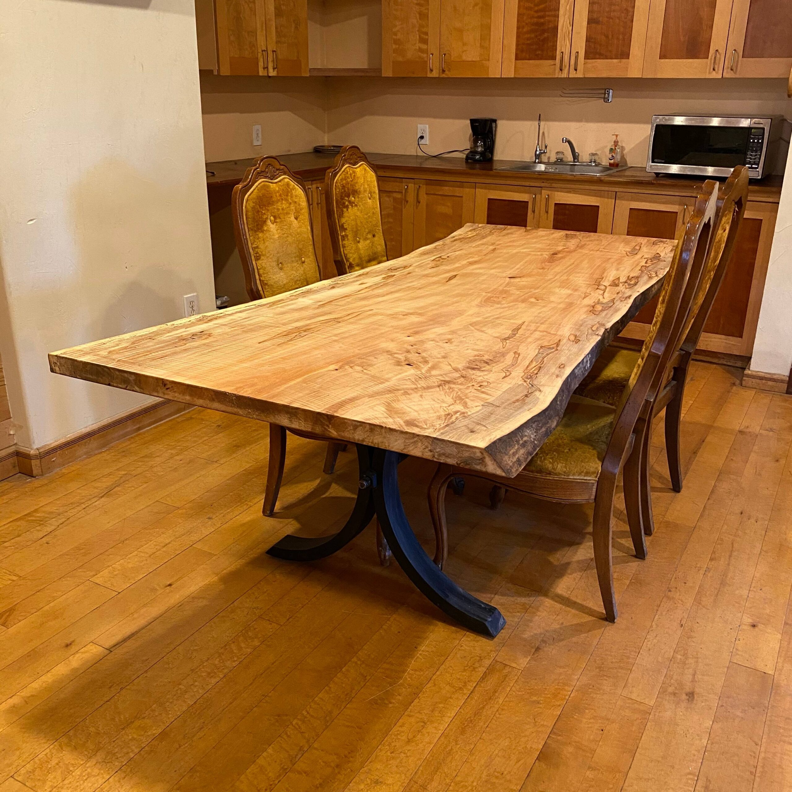 An unfinished maple slab planed and sanded sitting on one of our custom table bases.