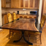 A reverse river table featuring black epoxy and a walnut slab.