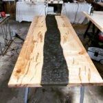 A finished ambrosia maple slab epoxy river tabletop.
