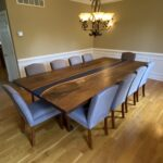 A large walnut river table for a dining room.